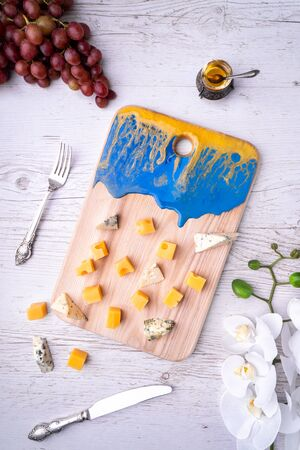 Composition cutting board with an abstract pattern, cheese, honey grapes, orchid flowers, on a light wooden tabletop. Zdjęcie Seryjne - 129212015
