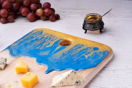 Composition cutting board with an abstract pattern, cheese, honey grapes, orchid flowers, on a light wooden tabletop.