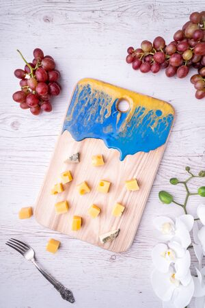 Composition cutting board with an abstract pattern, cheese, honey grapes, orchid flowers, on a light wooden tabletop. Zdjęcie Seryjne - 129212042