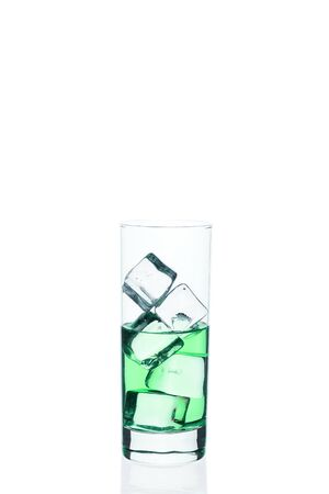 Green drink with ice cubes in a glass on a white Zdjęcie Seryjne