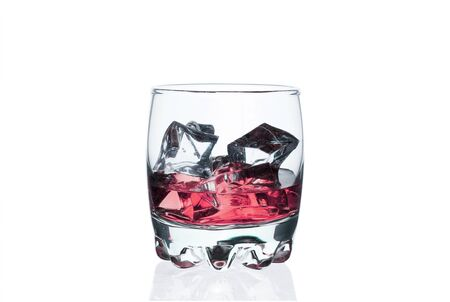 Pink drink with ice cubes in a glass on a white Zdjęcie Seryjne