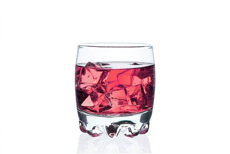 Pink drink with ice cubes in a glass on a white 写真素材