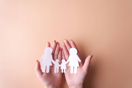 Female tender hands with a family symbol cut out of white paper.