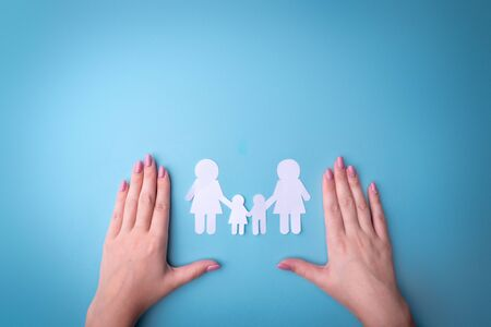 Female tender hands with a family symbol cut out of white paper Zdjęcie Seryjne - 130954622