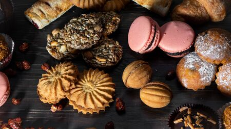 Cookies, muffins, croissants, pasta baking sweets sprout style on a wooden table.