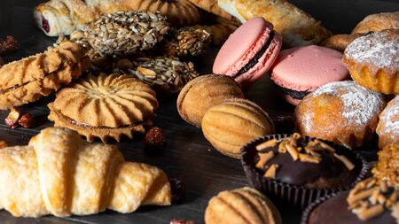 Cookies, muffins, croissants, pasta baking sweets sprout style on a wooden table. Zdjęcie Seryjne - 130954593