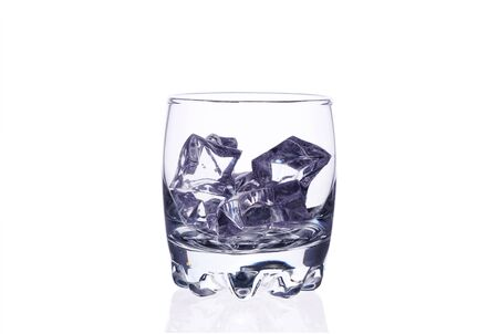 Glass of whiskey with ice cubes on a white background isolate. Zdjęcie Seryjne
