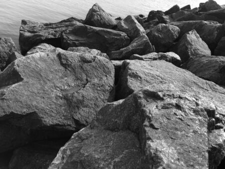 Granite stones on the seashore. Black-and-white photo. Contrasting, good texture. Nature pattern.