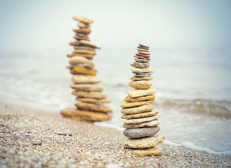 Stones pyramid on sand symbolizing zen, harmony, balance.