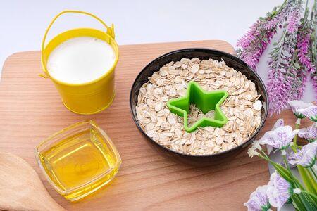 Natural oatmeal flakes, healthy food ingredients with vitamins. Ingredients for making breakfast, oatmeal, bucket of milk, honey. Zdjęcie Seryjne