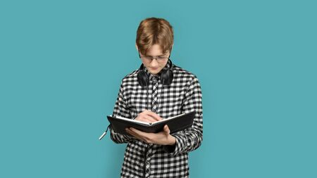 Teenager with red hair in a screeched shirt on a colored background. In glasses, with a notebook for school, he reads the assignment. Zdjęcie Seryjne