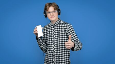 Teenager with red hair in a screeched shirt on a colored background. In reading glasses, with headphones on his head, he holds the player in his hand and shows the like.