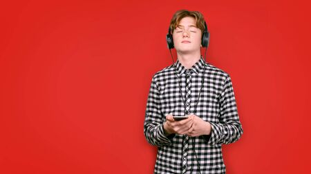 Teenager with red hair in a screeched shirt on a colored background. He closed his eyes while listening to music, with headphones on his head and a player in his hands. Zdjęcie Seryjne