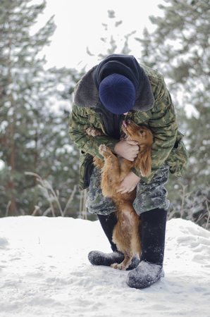 Warmly dressed man embracing loveful young russian spaniel dog with exposed tongue in the winter forest Stock fotó