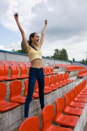 Beautiful teen girl supporter fan is happy while alone watching game at the stadium.