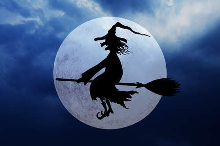 Halloween witch. Silhouette of smiling wicked witch flying on broomstick with hat with a wart on the nose on dark spooky night cloudy sky background. Stock Photo