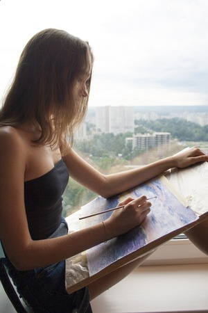 Young woman is drawing a watercolor painting. The female artist paints watercolour landscape. Teen girl with blond hair is sitting on the window sill with brush in hand. Creative concept.