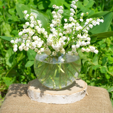 Lily of the valley bouquet in a glass vase outdoors