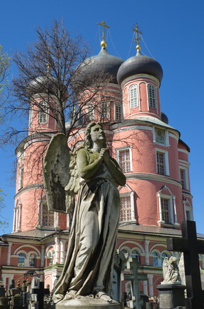 Donskoy monastery, Moscow, Russia. Vintage tombstone with a sculpture of an angel on the background of the Big (New)
