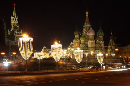 Christmas illuminations on the Big Moskvoretsky bridge, Moscow, Russia. St. Basils Cathedral and Spasskaya Tower of the Moscow Kremlin