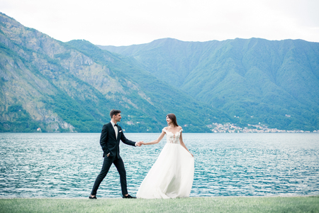 wedding couple running along the grass against the background of the lake and mountains Archivio Fotografico