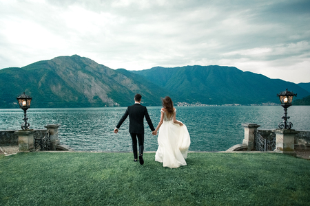 wedding couple running along the grass against the background of the lake and mountains Stock Photo