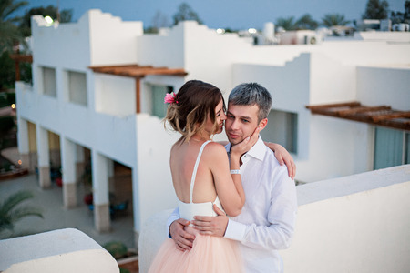 Newlyweds after the wedding in a luxury resort. Romantic bride and groom kiss on the roof of the hotel. Honeymoon. Tropical country. Wedding couple.