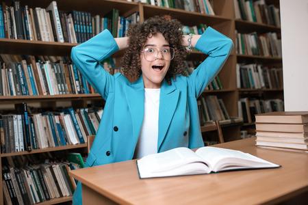 Jeune belle fille frisée à lunettes et costume bleu assis avec des livres dans la bibliothèque. Étudiant Étude