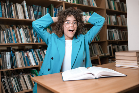 Junges schönes lockiges Mädchen mit Brille und blauem Anzug sitzt mit Büchern in der Bibliothek. Studentenstudium