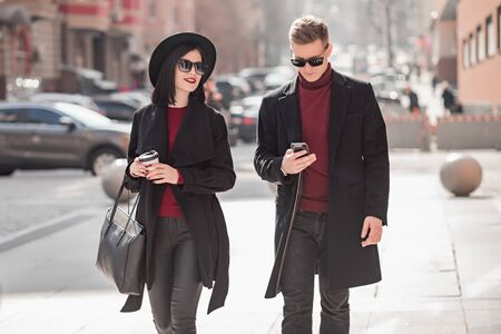 handsome young man and beautiful young woman in a black coat go and look at the phone on the street