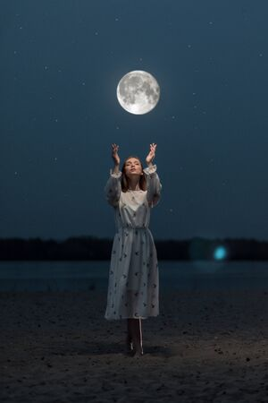 Young attractive girl in a long white dress on the beach stretches her arms to the moon Stock Photo