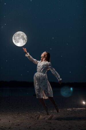 Young attractive girl in a long white dress on the beach stretches her arms to the moon