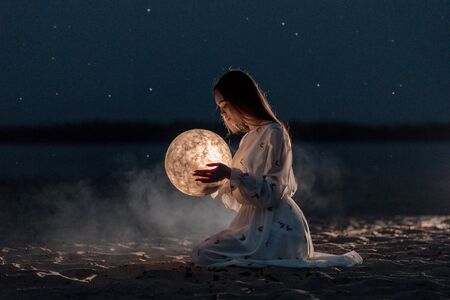 Beautiful young attractive girl on a night beach with sand and stars holds the moon in her hands Stockfoto