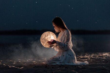 Hermosa joven atractiva en una playa de noche con arena y estrellas sostiene la luna en sus manos