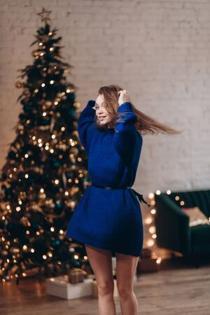 Young attractive woman in a blue sweater on the background of the New Year tree. New Year