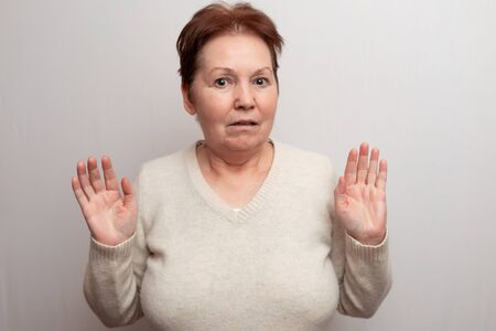 Old woman on a white background in a light sweater. Emotions