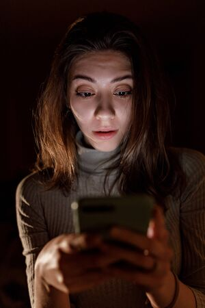 Smiling young woman texting on phone at night on a black background Фото со стока