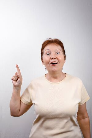 beautiful senior woman shows a hand to the side on a white background in a light T-shirt. emotions. isolated Stock fotó