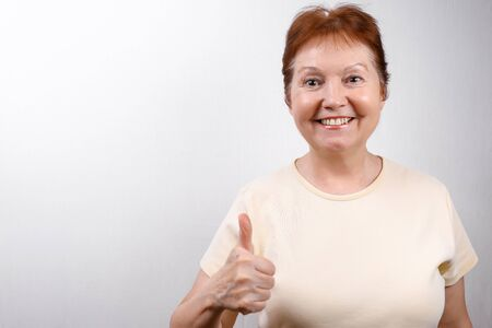beautiful senior woman looks in surprise at the frame on a white background in a light T-shirt. emotions 版權商用圖片