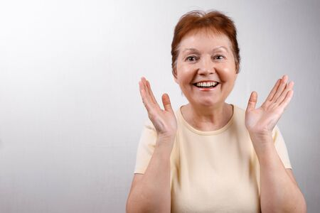beautiful senior woman looks in surprise at the frame on a white background in a light T-shirt. emotions