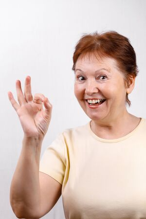 beautiful senior woman shows okay on a white background in a light T-shirt. place for text. isolated