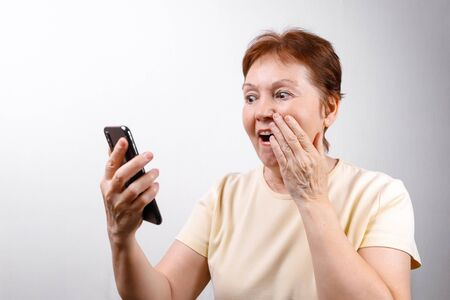 senior woman looks in surprise at the phone on a white background in a light T-shirt. place for text. isolated