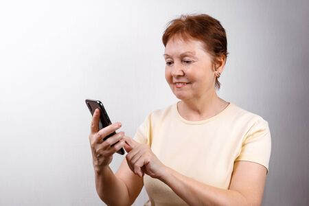 senior woman looks at the phone on a white background in a light T-shirt. place for text. isolated