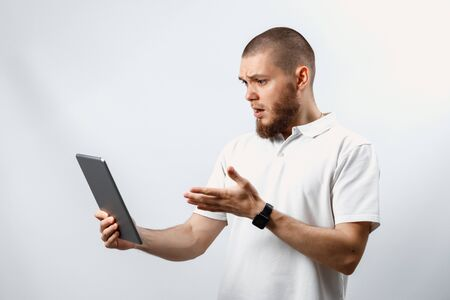 Portrait of a handsome happy bearded man in a white T-shirt with a tablet on a white background. isolated. emotions Фото со стока