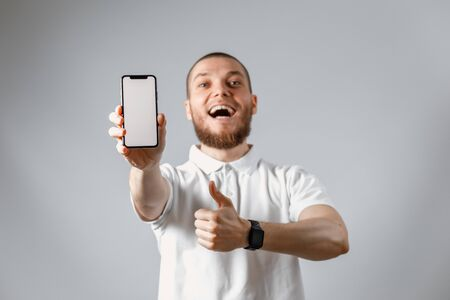 Portrait of a happy young man in a white t-shirt showing a phone screen on a gray background. isolated. Copyspace Фото со стока