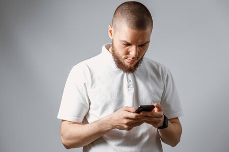 Portrait of a happy young man in a white T-shirt carefully looking at the phone on a gray background. isolated. Copyspace