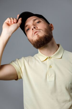 Portrait of a serious young man in a yellow T-shirt and black cap looking in frame on a gray background. isolated. Copyspace