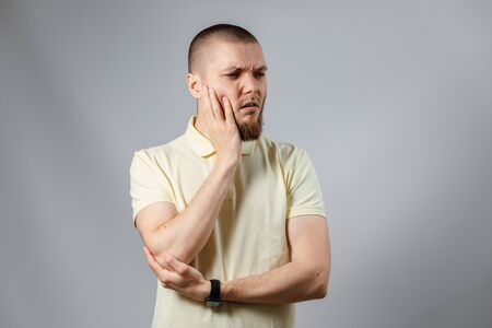 Portrait of a young man in a yellow T-shirt holding his cheek looking to the side on a gray background. isolated. tooth pain
