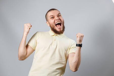 Portrait of a young man in a yellow T-shirt rejoices in victory on a gray background. isolated, copyspace