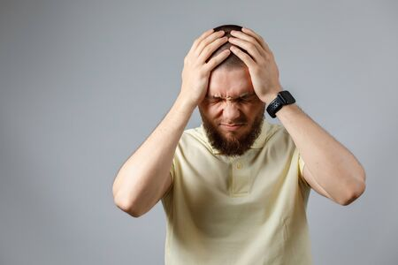 Portrait of a young upset man in a yellow t-shirt holding his head on a gray background. isolated. copyspace.